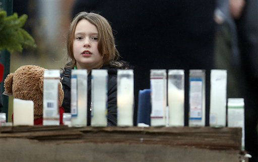 A young girl holding a teddy bear looks at a makeshift memorial outside of St. Rose of Lima Roman Catholic Church, Sunday, Dec. 16, 2012, in Newtown, Conn. On Friday, a gunman allegedly killed his mother at their home and then opened fire inside the Sandy Hook Elementary School in Newtown, killing 26 people, including 20 children.&#40;AP Photo&#47;Julio Cortez&#41; <span class=meta>(AP Photo&#47; Julio Cortez)</span>