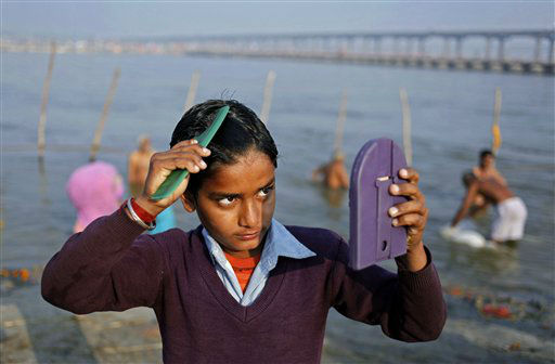 A young Indian Hindu devotee combs his hair after a dip at the Sangam, the confluence of the Ganges, Yamuna and mythical Saraswati River, during the Maha Kumbh festival in Allahabad, India, Thursday, Feb. 21, 2013. Millions of Hindu pilgrims have been attending the Maha Kumbh festival, which is one of the world&#39;s largest religious gatherings that lasts 55 days and falls every 12 years. &#40;AP Photo&#47; Rajesh Kumar Singh&#41; <span class=meta>(AP Photo&#47; Rajesh Kumar Singh)</span>