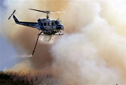 "<div class=""meta ""><span class=""caption-text "">A Kern County Fire helicopter makes a water drop on a hotspot over a hill near Thousand Oaks, Calif. on Thursday, May 2, 2013. Authorities have ordered evacuations of a neighborhood and a university about 50 miles west of Los Angeles where a wildfire is raging close to subdivisions. The blaze on the fringes of Camarillo and Thousand Oaks broke out Thursday morning and was quickly spread by gusty Santa Ana winds. Evacuation orders include California State University, Channel Islands. (AP Photo/Nick Ut) (AP Photo/ Nick Ut)</span></div>"