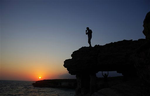 "<div class=""meta ""><span class=""caption-text "">People enjoy the sunset by the sea at the caves area in Ayia Napa resort near Cavo Greco in southeast of capital Nicosia, Cyprus, Sunday, Aug. 5,  2012. (AP Photo/Petros Karadjias) (AP Photo/ Petros Karadjias)</span></div>"