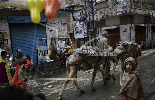 "<div class=""meta ""><span class=""caption-text "">With election banners showing cricket star-turned-politician, and leader of Pakistan Tehreek-e-Insaf party, Imran Khan, and other member of his party, a Pakistani daily laborer walks his donkeys past children playing in a neighborhood in Rawalpindi, Pakistan, Sunday, May 12, 2013. Pakistan's former prime minister Nawaz Sharif looked set Sunday to return to power for a third term, with an overwhelming election tally that just weeks ago seemed out of reach for a man who had been ousted by a coup and was exiled abroad before clawing his way back as an opposition leader. (AP Photo/Muhammed Muheisen) (AP Photo/ Muhammed Muheisen)</span></div>"