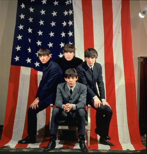 The Beatles, clockwise from top center, John Lennon, George Harrison, Paul McCartney and Ringo Starr, pose with an American flag in a Paris photo studio prior to their first visit to the United States in January 1964. &#40;AP Photo&#47;Copyright Applecorps Ltd. &#41; <span class=meta>(AP Photo&#47; Anonymous)</span>