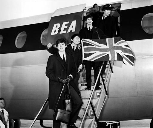 The Beatles, from front, Paul McCartney, George Harrison, Ringo Starr, and John Lennon, wave a Union Jack flag as they arrive from Paris at London Airport in London, England, on Feb. 5, 1964.  &#40;AP Photo&#47;Victor Boyton&#41; <span class=meta>(AP Photo&#47; VICTOR BOYTON)</span>