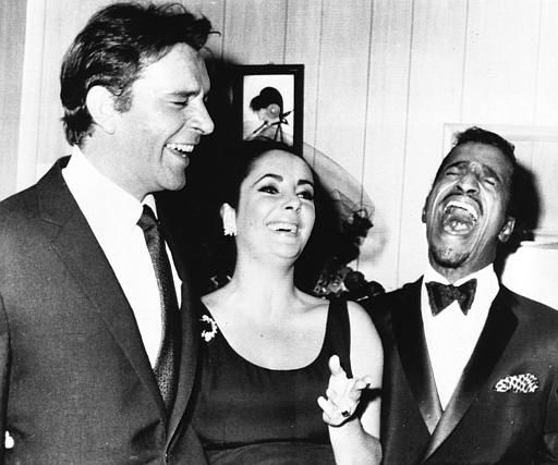 "<div class=""meta image-caption""><div class=""origin-logo origin-image ""><span></span></div><span class=""caption-text"">British actress Elizabeth Taylor and husband Richard Burton share a joke with U.S entertainer Sammy Davis Jnr., in Davis' dressing room after his opening at New York's Copacabana night club, April. 30, 1964. (AP Photo) (AP Photo/ XKR)</span></div>"