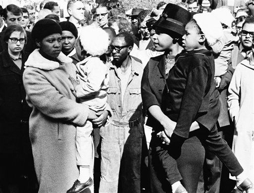 Outside the Palace of Justice, Winnie Mandela &#40;right&#41; waits for a glimpse of her husband, Nelson Mandela , as he and seven other men are carried off to jail in Blacn Marias on June 12, 1964 in Pretoria, South Africa. The men had been convicted of sabotage and sentenced to life imprisonment. Mrs. Mandela waited in vain  the police van took another route and did not pass her. &#40;AP Photo&#47;ARG&#41; <span class=meta>(AP Photo&#47; ARG)</span>