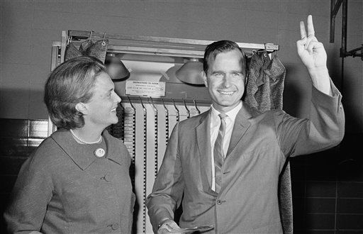 Republican Senatorial candidate George Bush shows a victory sign as he and his wife Barbara stand in front of a vote machine November 3, 1964 in Houston,Tex., just before casting their ballot.   The candidate waited an hour and a half in a long of votes that circled the Pilgrim Elementary School where the Bush&#39;s voted this morning. in Houston.    &#40;AP Photo&#41;. <span class=meta>(AP Photo&#47; Anonymous)</span>
