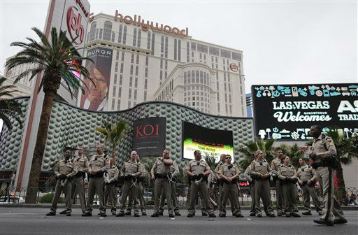 Las Vegas Metropolitan Police officers stand along Las Vegas Boulevard during a demonstration by Culinary Workers Union members, Wednesday, March 20, 2013, in Las Vegas. Nearly 98 protestors were arrested during the demonstration in which they sat on and blocked traffic along Las Vegas Boulevard. Workers have been in contract talks with Cosmopolitan Las Vegas owner Deutsche  Bank for two years. &#40;AP Photo&#47;Julie Jacobson&#41; <span class=meta>(AP Photo&#47; Julie Jacobson)</span>