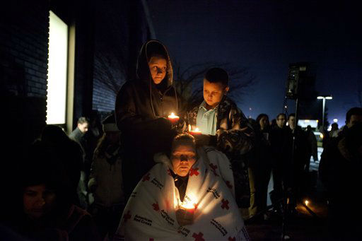 Sharon Bertrand, center, listens with her daughter Daysha, 13, left, and son Juan, all of Waterbury, Conn., to a memorial service over a loudspeaker outside Newtown High School for the victims of the Sandy Hook Elementary School shooting, Sunday, Dec. 16, 2012, in Newtown, Conn. &#40;AP Photo&#47;David Goldman&#41; <span class=meta>(AP Photo&#47; David Goldman)</span>