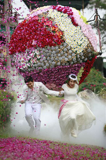 Prasit Rangsitwong, left, and Varutton Rangsitwong run away from a giant flower ball as a part of an adventure-themed wedding ceremony in Prachinburi province, Thailand, Wednesday, Feb. 13, 2013, on the eve of Valentine&#39;s Day. &#40;AP Photo&#47;Wason Wanichakorn&#41; <span class=meta>(AP Photo&#47; Wason Wanichakorn)</span>