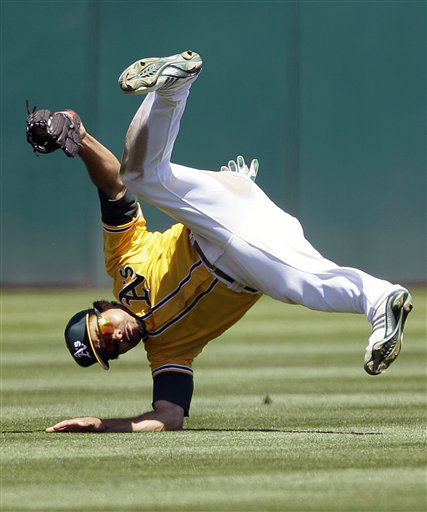 Oakland Athletics center fielder Coco Crisp goes tumbling after catching a fly ball hit by Texas Rangers&#39; Craig Gentry during the seventh inning of their baseball game on Wednesday, July 18, 2012, in Oakland, Calif. &#40;AP Photo&#47;Eric Risberg&#41; <span class=meta>(AP Photo&#47; Eric Risberg)</span>