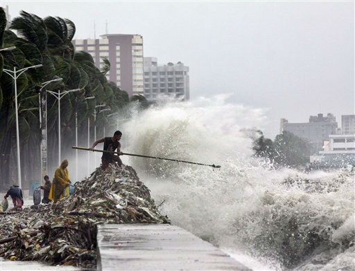 A man holding a pole stay on the mound of garbage washed ashore by big waves as others look for recyclable materials Wednesday, Aug. 1, 2012 along Roxas Blvd. in Manila, Philippines. The slow-moving Typhoon Saola killed at least 12 people and displaced 154,000 in the Philippines. &#40;AP Photo&#47;Pat Roque&#41; <span class=meta>(AP Photo&#47; Pat Roque)</span>
