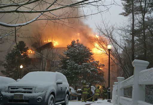 Firefighters battle a 4-alarm fire in a 3-story apartment building in Wilmington, Mass. Friday, Feb. 8, 2013, during a major winter snowstorm. Up to 2 feet of snow is expected in the Boston area that has seen mostly bare ground this winter. &#40;AP Photo&#47;Elise Amendola&#41; <span class=meta>(AP Photo&#47; Elise Amendola)</span>