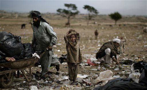 Afghan refugee girl, Areeba Mohammed, 5, center, talks with a girl, not pictured, while she and her father, seen left pushing a cart, collect useful items from a pile of garbage left in a field next to a slum where they live, on the outskirts of Islamabad, Pakistan, Tuesday, Oct. 23, 2012. &#40;AP Photo&#47;Muhammed Muheisen&#41; <span class=meta>(AP Photo&#47; Muhammed Muheisen)</span>