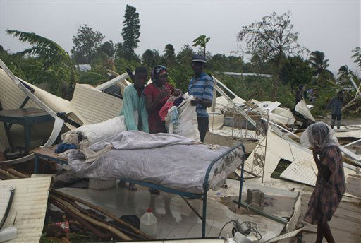 A family salvages what is left of their home at a camp set up for people displaced by the 2010 earthquake that was destroyed by Tropical Storm Isaac in Port-au-Prince, Haiti, Saturday Aug. 25, 2012. Tropical Storm Isaac swept across Haiti&#39;s southern peninsula early Saturday, dousing a capital city prone to flooding and adding to the misery of a poor nation still trying to recover from the 2010 earthquake. &#40;AP Photo&#47;Dieu Nalio Chery&#41; <span class=meta>(AP Photo&#47; Dieu Nalio Chery)</span>