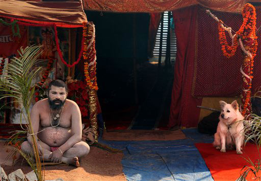 A naked Hindu holy man or a Naga Sadhu and his dog watch as devotees walk past his tent at Sangam, the confluence of the rivers Ganges, Yamuna and mythical Saraswati during the Maha Kumbh Mela, in Allahabad, India, Tuesday, Jan. 15, 2013. Millions of devout Hindus led by naked ascetics with ash smeared on their bodies plunged into the frigid waters of India&#39;s holy Ganges River on Monday in a ritual they believe can wash away their sins. The ceremony in the northern city of Allahabad took place on the most auspicious day of the Kumbh Mela, or Pitcher Festival, one of the world&#39;s largest religious gatherings that lasts 55 days. &#40;AP Photo&#47;Manish Swarup&#41; <span class=meta>(AP Photo&#47; Manish Swarup)</span>