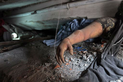 A victim&#39;s body is trapped in rubble after an eight-story building housing several garment factories collapsed in Savar, near Dhaka, Bangladesh, Wednesday, April 24, 2013. Dozens were killed and many more are feared trapped in the rubble. &#40;AP Photo&#47; A.M. Ahad&#41; <span class=meta>(AP Photo&#47; A.M. Ahad)</span>