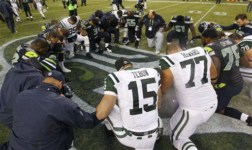 New York Jets&#39; Tim Tebow &#40;15&#41; kneels with other players in a prayer circle after the Jets lost to the Seattle Seahawks during an NFL football game, Sunday, Nov. 11, 2012, in Seattle. The Seahawks won 28-7. &#40;AP Photo&#47;Elaine Thompson&#41; <span class=meta>(AP Photo&#47; Elaine Thompson)</span>