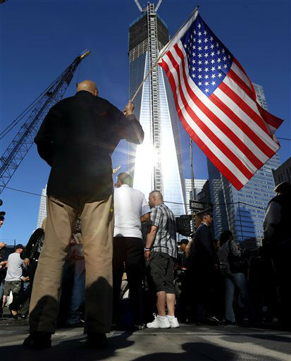 "<div class=""meta image-caption""><div class=""origin-logo origin-image ""><span></span></div><span class=""caption-text"">Marcio Rodriguez holds a United States flag as he pays respects in front of the construction site of One World Trade Center during the 11th anniversary of the Sept. 11 terrorist attacks, Tuesday, Sept. 11, 2012, in New York. (AP Photo/Julio Cortez) (AP Photo/ Julio Cortez)</span></div>"