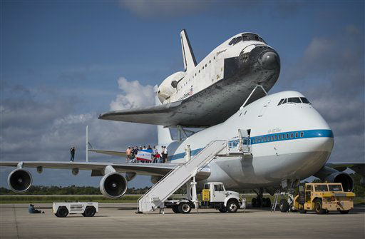 This photo provided by NASA shows workers posing for a photograph on the wing of NASA&#39;s Shuttle Carrier Aircraft, &#40;SCA&#41; with the space shuttle Endeavour placed on top, at the NASA Kennedy Space Center, Shuttle Landing Facility on Tuesday, Sept. 18, 2012 in Cape Canaveral, Fla. The SCA, a modified 747 jetliner, will fly Endeavour to Los Angeles where it will be placed on public display at the California Science Center. This is the final ferry flight scheduled in the Space Shuttle Program era. &#40;AP Photo&#47;NASA, Bill Ingalls&#41; <span class=meta>(AP Photo&#47; Bill Ingalls)</span>