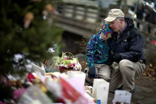 David Freedman, right, kneels with his son Zachary, 9, both of Newtown, Conn., as they visit a sidewalk memorial for the Sandy Hook Elementary School shooting victims, Sunday, Dec. 16, 2012, in Newtown, Conn. A gunman walked into Sandy Hook Elementary School in Newtown Friday and opened fire, killing 26 people, including 20 children. &#40;AP Photo&#47;David Goldman&#41; <span class=meta>(AP Photo&#47; David Goldman)</span>
