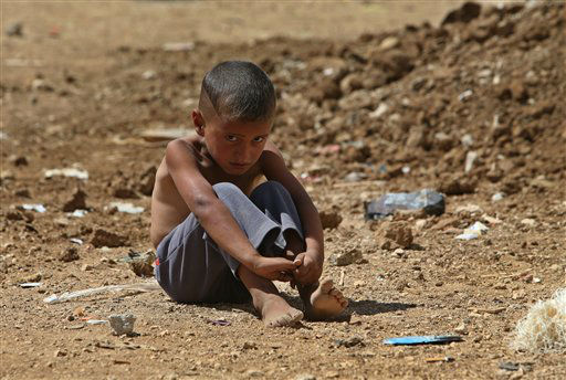 A Syrian refugee boy sits on the ground at a temporary refugee camp, in the eastern Lebanese Town of Al-Faour, Bekaa valley near the border with Syria, Lebanon, Wednesday, Sept. 11, 2013. Lebanon is a tiny country that shares a porous border with Syria, and has seen cross-border shelling, sectarian clashes and car bombings in recent months related to the civil war raging next door. The country of 4.5 million already is already host to nearly 1 million Syrian refugees. (AP Photo/Hussein Malla)
