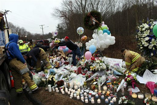 Firefighters and other volunteers reorganize a memorial for shooting victims near Sandy Hook Elementary School before erecting a shelter over it, Sunday, Dec. 16, 2012 in Newtown, Conn.  A gunman walked into Sandy Hook Elementary School in Newtown Friday and opened fire, killing 26 people, including 20 children. &#40;AP Photo&#47;Jason DeCrow&#41; <span class=meta>(AP Photo&#47; Jason DeCrow)</span>