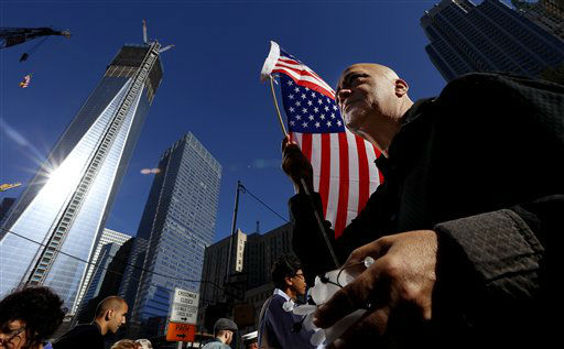 Marcio Rodriguez holds a United States flag as he pays respects in front of the construction site of One World Trade Center during the 11th anniversary of the Sept. 11 terrorist attacks, Tuesday, Sept. 11, 2012, in New York. &#40;AP Photo&#47;Julio Cortez&#41; <span class=meta>(AP Photo&#47; Julio Cortez)</span>