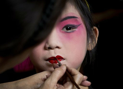 A girl is applied a makeup before a training at Peking Opera summer camp organized by the Peking Opera House in Beijing, China Tuesday, Aug. 14, 2012. The summer training course was held to attract the public to Chinese traditional performance. &#40;AP Photo&#47;Andy Wong&#41; <span class=meta>(AP Photo&#47; Andy Wong)</span>