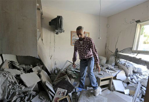 An Israeli man walks in the rubble of a house hit by a rocket fired by militants from Gaza Strip, in the southern city of Beersheba, Israel, Tuesday, Nov. 20, 2012. Efforts to end a week-old convulsion of Israeli-Palestinian violence drew in the world's top diplomats on Tuesday, with President Barack Obama dispatching his secretary of state to the region on an emergency mission and the U.N. chief appealing from Cairo for an immediate cease-fire.(AP Photo/Tsafrir Abayov)