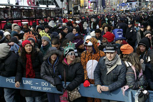 People who arrived Monday morning Dec. 31, 2012, line a front row spot to watch the ball drop in Times Square in New York.  An estimated 1 million people were expected to cram into district to see the crystal ball drop and countdown to 2013, organizers said.  &#40;AP Photo&#47;Seth Wenig&#41; <span class=meta>(AP Photo&#47; Seth Wenig)</span>