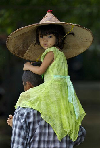 A child is carried by an adult in Khanaung Chaung Wa village, southeast of Yangon Myanmar, Wednesday, June 5, 2013. &#40;AP Photo&#47;Gemunu Amarasinghe&#41; <span class=meta>(AP Photo&#47; Gemunu Amarasinghe)</span>