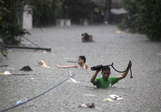 Men crosses deep floodwaters in San Juan, north of Manila, Philippines, on Wednesday Aug. 8, 2012.  Widespread flooding paralyzed the Philippine capital and many other areas on Wednesday as rescue efforts focused on the large number of distressed residents who are still marooned on their roof tops and unable to move to high ground. &#40;AP Photo&#47;John Javellana&#41; <span class=meta>(AP Photo&#47; JOHN JAVELLANA)</span>