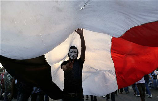 An opponent of Egypt&#39;s Islamist President Mohammed Morsi wearing a Guy Fawkes mask flashes the victory sign under a large Egyptian national flag during a protest outside the presidential palace, in Cairo, Egypt, Tuesday, July 2, 2013. Egypt was on edge Tuesday following a &#34;last-chance&#34; ultimatum the military issued to Mohammed Morsi, giving the president and the opposition 48 hours to resolve the crisis in the country or have the army step in with its own plan. &#40;AP Photo&#47;Hassan Ammar&#41; <span class=meta>(AP Photo&#47; Hassan Ammar)</span>