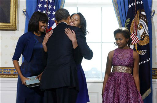 President Barack Obama hugs daughter Malia as first lady Michelle Obama and daughter Malia watch after Obama was officially sworn-in by Chief Justice John Roberts, not pictured, in the Blue Room of the White House during the 57th Presidential Inauguration in Washington, Sunday, Jan. 20, 2013.  &#40;AP Photo&#47;Larry Downing, Pool&#41; <span class=meta>(AP Photo&#47; LARRY DOWNING)</span>