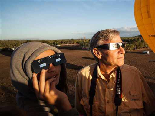 In this photo released by Hot Air Balloon Cairns, Hank Harper, right, of  Los Angeles watches the solar eclipse from a hot air balloon near Cairns, Australia, Wednesday, Nov. 14, 2012. Harper flew to Australia with his two children specially to watch the full eclipse, saying we &#34;watched the sun?s rays re-emerge from behind the moon while kangaroos hopped along the ground below.&#34; &#40;AP Photo&#47;Hot Air Balloon Cairns&#41; <span class=meta>(AP Photo&#47; Uncredited)</span>