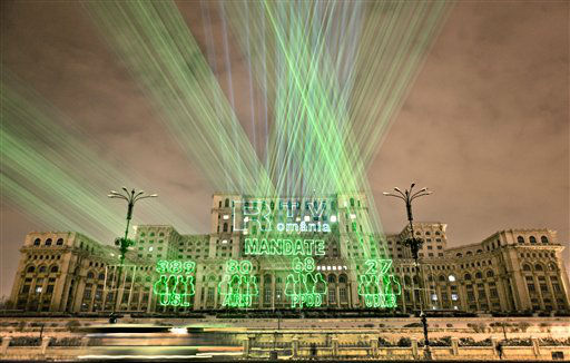 Lasers project the number of seats won in the parliamentary elections by the political groups that received over the minimum 5 percent of the votes, on the facade of the communist era built Palace of Parliament in Bucharest, Romania, Monday night, Dec. 10, 2012. Partial results show Romania?s ruling center-left alliance Social Liberal Union won about 59 percent of the seats in the 452-seat legislature, followed by a center-right group allied to President Traian Basescu that polled just below 17 percent. A populist party lead by a media tycoon scored about 14 percent in Sunday?s election and an ethnic Hungarian party won just over 5 percent. &#40;AP Photo&#47;Vadim Ghirda&#41; <span class=meta>(AP Photo&#47; Vadim Ghirda)</span>