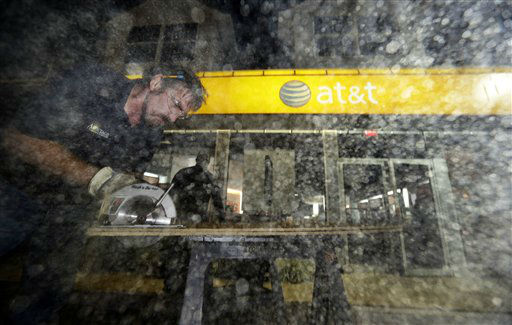 Sawdust flies in the air as Brian Rogers, left, cuts a board with a circular saw, as he and Dwayne Wallace board up an AT&#38;T store in Rehoboth Beach, Del. on Saturday, Oct. 27, 2012 as Hurricane Sandy approaches the east coat. &#40;AP Photo&#47;Alex Brandon&#41; <span class=meta>(AP Photo&#47; Alex Brandon)</span>