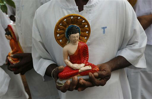 A Sri Lankan inmate of the Welikada prison holds a statue of Lord Buddha as he takes part in a religious ceremony on the eve of the new year on Monday, Dec. 31, 2012.  Inmates of the Welikada prison, one of the largest prisons in Sri Lanka housing over four thousand prisoners, invoked blessings and ushered in the new year by engaging in Buddhist rituals. &#40;AP Photo&#47;Eranga Jayawardena&#41; <span class=meta>(AP Photo&#47; Eranga Jayawardena)</span>