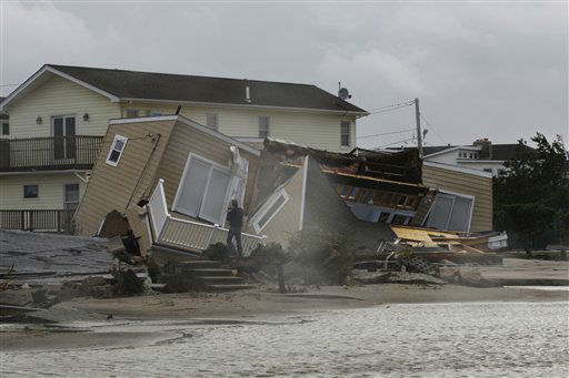 A man photographs a home damaged during a storm at Breezy Point in the New York City borough of Queens Tuesday, Oct. 30, 2012.  The fire destroyed between 80 and 100 houses Monday night in an area flooded by the superstorm that began sweeping through earlier. &#40;AP Photo&#47;Frank Franklin II&#41; <span class=meta>(AP Photo&#47; Frank Franklin II)</span>