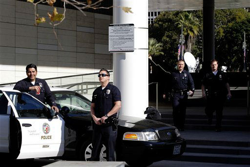 Los Angeles police officers stand alert at the LAPD headquarters in Los Angeles on Tuesday, Feb. 12, 2013. Police are now investigating more than 1,000 tips from the public in the search for the Christopher Dorner, who is suspected of a deadly revenge plot against the Los Angeles Police Department.  The number of tips has grown from an initial 250 since the city offered a &#36;1 million reward for information leading to the capture of Dorner. &#40;AP Photo&#47;Nick Ut&#41; <span class=meta>(AP Photo&#47; Nick Ut)</span>
