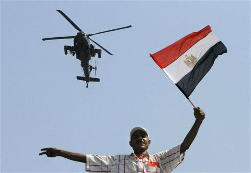 An military helicopter flies over an opponent if Egyptian Islamist President Mohammed Morsi as he waves a national flag, in Tahrir Square in Cairo, Egypt, Tuesday, July 2, 2013. With a military deadline for intervention ticking down, protesters seeking the ouster of Egypt&#39;s Islamist president sought Tuesday to push the embattled leader further toward the edge with another massive display of people power.&#40;AP Photo&#47;Amr Nabil&#41; <span class=meta>(AP Photo&#47; Amr Nabil)</span>