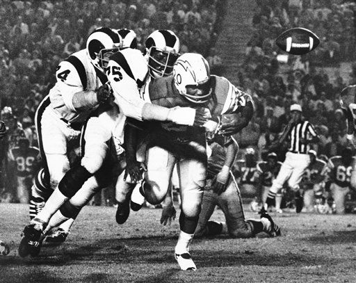 The Rams&#39; David &#40;Deacon&#41; Jones has little Mike Garrett in his grip and the ball is flying loose on an interrupted left-end sweep by the Chargers at Los Angeles, Sept. 4, 1971. Tackle Merlin Olsen backs up Jones at left. San Diego recovered the fumble and went on to win the exhibition, 20-14. &#40;AP Photo&#47;David F. Smith&#41; <span class=meta>(AP Photo&#47; David F. Smith)</span>