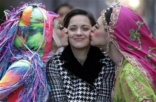 "<div class=""meta ""><span class=""caption-text "">Actress Marion Cotillard, of France, center, the Hasty Pudding Woman of the Year, is kissed by Harvard University theatrical students Renee Rober, left, and Ben Moss, right, as they ride in the back of a convertible during a parade through Harvard Square, in Cambridge, Mass., Thursday, Jan. 31, 2013. The award was presented to Cotillard by Hasty Pudding Theatricals, a theatrical student society at Harvard University. (AP Photo/Steven Senne) (AP Photo/ Steven Senne)</span></div>"