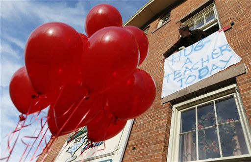 Gary Seri, general manager at the Stone River Grille, hangs a message written on a table cloth in honor of the teachers who died along with students a day earlier when a gunman open fire at Sandy Hook Elementary School, Saturday, Dec. 15, 2012, in the Sandy Hook village of Newtown, Conn. Seri, who put up red balloons that were not used when a sweet 16 party was canceled the night before in light of the massacre, said the teachers were scheduled to have their holiday party at his restaurant. The massacre of 26 children and adults at Sandy Hook Elementary school elicited horror and soul-searching around the world even as it raised more basic questions about why the gunman, 20-year-old Adam Lanza, would have been driven to such a crime and how he chose his victims.  &#40;AP Photo&#47;Julio Cortez&#41; <span class=meta>(AP Photo&#47; Julio Cortez)</span>