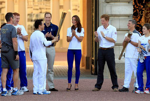 In this photo provided by LOCOG, Torchbearer 170 passes the Olympic Flame to Torchbearer 171 in front of Buckingham Palace in the presence of the Duke and Duchess of Cambridge and Prince Harry on the Torch Relay leg through Westminster, Thursday, July 26, 2012, in London. The opening ceremonies for the 2012 Summer Olympics will be held Friday, July 27. &#40;AP Photo&#47;LOCOG, Gareth Fuller&#41; <span class=meta>(AP Photo&#47; Gareth Fuller)</span>