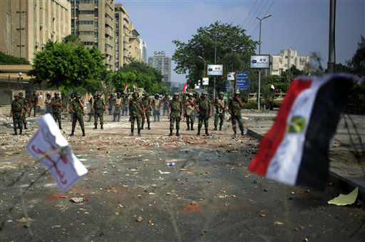 A national flag waves on the barbed wire as army soldiers guard at the Republican Guard building in Nasr City, Cairo, Egypt, Tuesday, July 9, 2013. Egyptian security forces killed dozens of supporters of Egypt&#39;s ousted president in one of the deadliest single episodes of violence in more than two and a half years of turmoil. The toppled leader&#39;s Muslim Brotherhood called for an uprising, accusing troops of gunning down protesters, while the military blamed armed Islamists for provoking its forces. &#40;AP Photo&#47;Khalil Hamra&#41; <span class=meta>(AP Photo&#47; Khalil Hamra)</span>