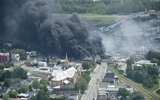 "<div class=""meta ""><span class=""caption-text "">Smoke rises from railway cars that were carrying crude oil after derailing in downtown Lac Megantic, Quebec, Canada, Saturday, July 6, 2013. A large swath of Lac Megantic was destroyed Saturday after a train carrying crude oil derailed, sparking several explosions and forcing the evacuation of up to 1,000 people. (AP Photo/The Canadian Press, Paul Chiasson) (AP Photo/ Paul Chiasson)</span></div>"