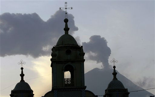 Church steeples are silhouetted against the active Tungurahua volcano, seen from Huambalo, Ecuador, Monday, Dec. 17, 2012.  The country&#39;s National Geophysics Institute says that a constant plume of gas and ash is rising about half a mile &#40;1 kilometer&#41; above the crater, with ash falling on nearby communities.  &#40;AP Photo&#47;Dolores Ochoa&#41; <span class=meta>(AP Photo&#47; Dolores Ochoa)</span>