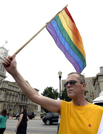 Aaron Bingham of Louisville, Ky., waves a rainbow flag during a rally in support of the U.S. Supreme Court decision on the Defense of Marriage Act, June 26, 2013, at Jefferson Square in Louisville, Ky. The justices issued two 5-4 rulings in their final session of the term. One decision wiped away part of a federal anti-gay marriage law that has kept legally married same-sex couples from receiving tax, health and pension benefits. The other was a technical legal ruling that said nothing at all about same-sex marriage, but left in place a trial court&#39;s declaration that California&#39;s Proposition 8 is unconstitutional.  &#40;AP Photo&#47;Timothy D. Easley&#41; <span class=meta>(AP Photo&#47; Timothy D. Easley)</span>