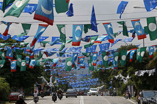 Motorists drive underneath flags of Malaysia&#39;s ruling party National Front, opposition Pan-Malaysian Islamic Party and People&#39;s Justice Party ahead of the upcoming general elections in Kuala Lumpur, Malaysia, Monday, April 29, 2013. With less than a week to general elections, Malaysia&#39;s opposition alliance is banking on the promise of bold change to end the governing coalition&#39;s 56-year rule. It says a new economic playing field will strip away decades of race-based policies that it believes bred corruption and hampered growth. &#40;AP Photo&#47;Lai Seng Sin&#41; <span class=meta>(AP Photo&#47; Lai Seng Sin)</span>